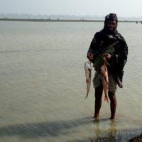 বিল কুমারী: ধৃত মাছ হাতে একজন মৎস্য শিকারী